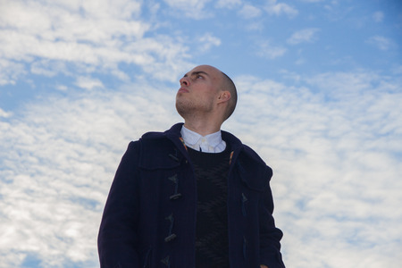 suite: Bald young man with brown eyes dressed in modern and stylish clothes on blue sky with clouds - business, work, fashion, goals, success concept.