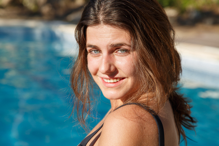 Portrait of young brunette smiling happily at camera while posing on background of pool. Stock Photo