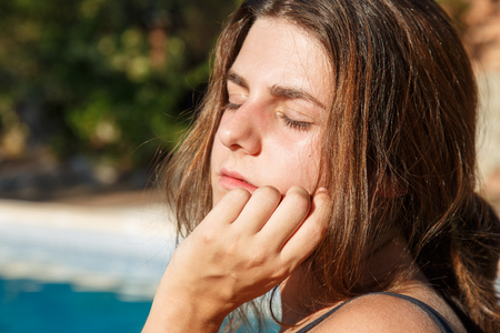 Portrait of young brunette with closed eyes posing on background of pool.