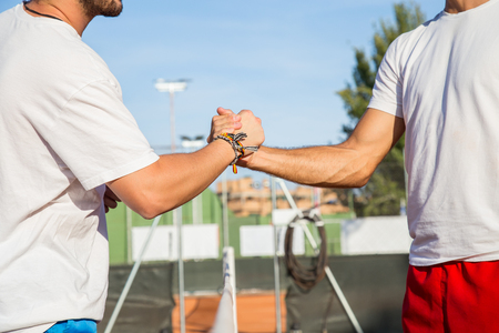 Two professional tennis players holding hands over tennis net before match. Stock Photo