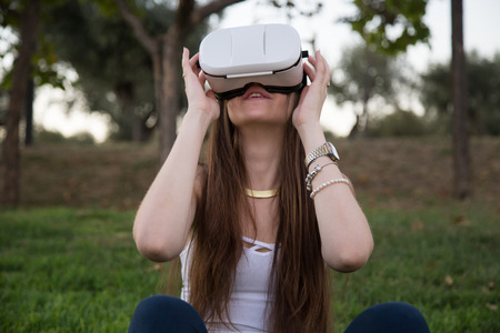 Young woman enjoying experience in VR glasses
