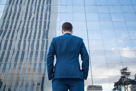 Back view of businessman in classy suit standing with hands in pockets on background of glass building.