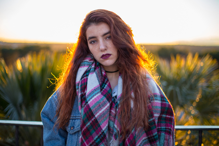 Young brunette in trendy denim jacket and scarf looking alluringly at camera in back lit on nature. Stock Photo