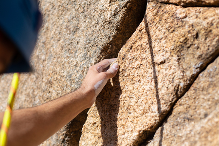 Close up hand of young man climber in a crack while climbing a wall on a sunny day. 스톡 콘텐츠
