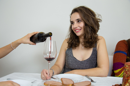 Young woman serving wine to her friend 版權商用圖片