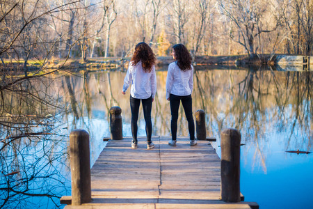 Back view of young twin sisters in the same clothes looking at lake on autumn day in the forest Archivio Fotografico