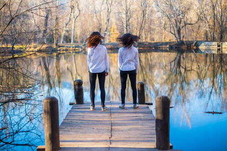 Back view of young twin sisters in the same clothes shaking hair at the lake on autumn day in the forest Archivio Fotografico