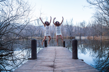 Cheerful twin sisters in white dresses jumping with hands up on wooden pier at calm lake on autumn day
