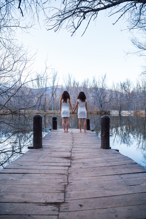 Back view of twin sisters in same white dresses holding hands while standing on wooden pier at calm lake on autumn day Archivio Fotografico