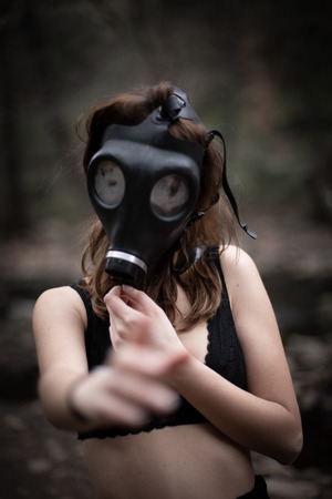 Portrait of anonymous woman in black clothes and gas mask standing in amazing spooky forest Stock Photo