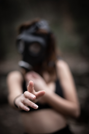 Portrait of anonymous woman in black clothes and gas mask standing in amazing spooky forest Banque d'images