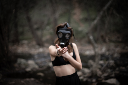 Portrait of anonymous woman in black clothes and gas mask standing in amazing spooky forest 版權商用圖片