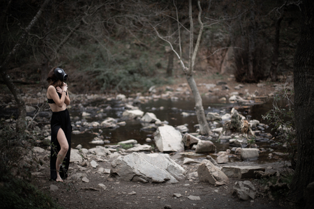 Side view of anonymous barefoot woman in black clothes and gas mask standing in amazing spooky forest