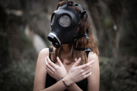 Portrait of anonymous woman in black clothes and gas mask standing in amazing spooky forest Banco de Imagens