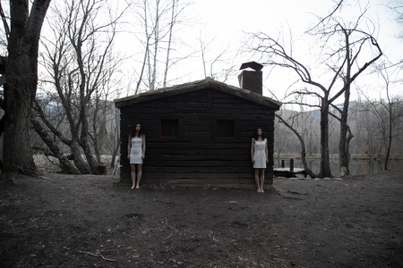 Young twin sisters in white dresses standing near abandoned wood house in mysterious forest