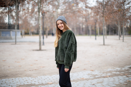 Portrait of happy smiling young woman with winter hat in a park in autumn