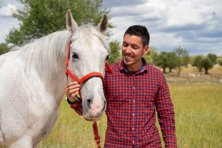 Young man touching white horse affectionately