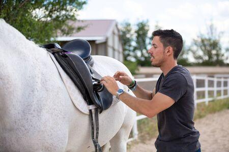 Seitenansicht eines jungen Mannes, der einen schwarzen Sattel auf dem Rücken eines weißen Pferdes anzieht, während er im Fahrerlager auf der Ranch steht? Standard-Bild