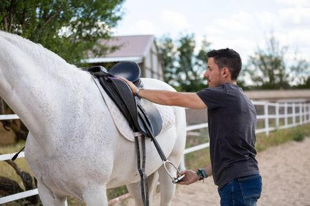 Side view of young guy putting on black saddle on back of white horse while standing in paddock on ranch 写真素材