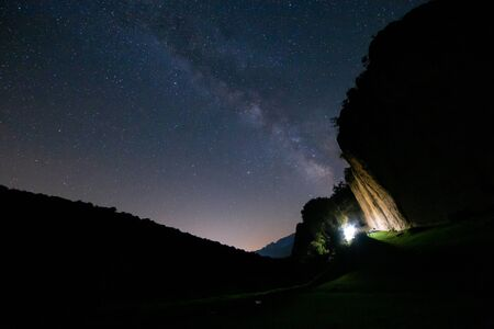 Picturesque view of shining stars and Milky Way on dark summer sky in mountains 写真素材 - 131995630