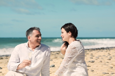 couples talking and laughing and sitting on the beach with champagne photo