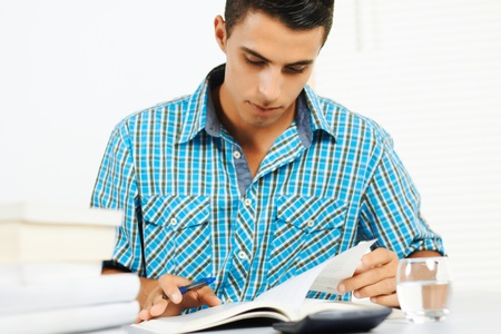 Young man reading and taking notes.