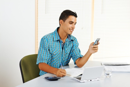 Cheerful young man receiving a call while you study. photo