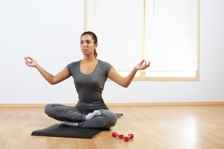 Beautiful Hispanic woman doing yoga at home Stock Photo - 10949653