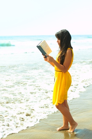 Portrait of a young lady reading a book on the beach photo