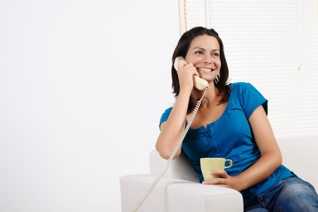 Portrait  of a beautiful young woman  laughing, talking on the phone and holding a cup. photo