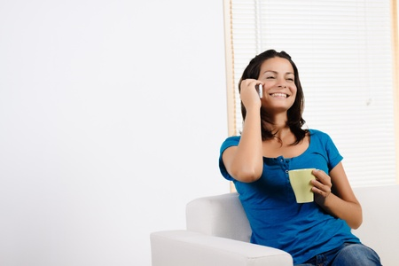 Portrait  of a beautiful young woman talking on a mobile phone and laughing. photo