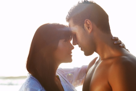 emotional couple: portrait of a  passionate couple in love  kissing and embracing between  backlit