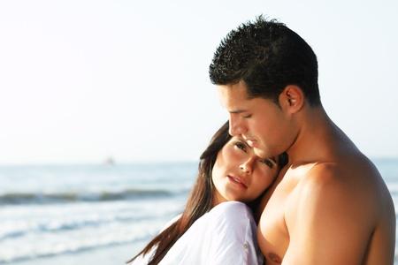страстный: крупным планом двойник любящей пары, глядючи для ширь с берега пляжа