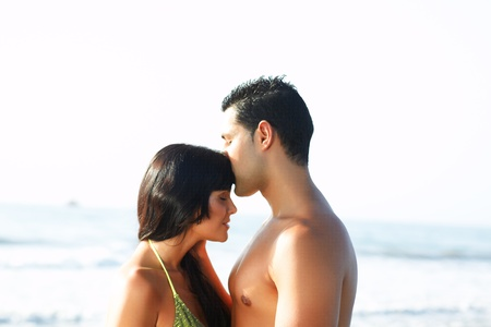 portrait of a  loving couple on the edge of  the beach. While he kisses her on the forehead photo