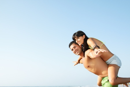 young couple fooling around on the beach photo