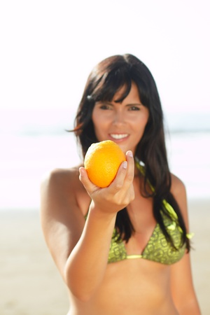sexy  women offering you an orange on the beach photo