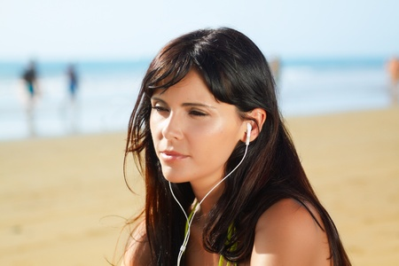 close up portrait of  a beautiful woman on the beach  listening to music photo