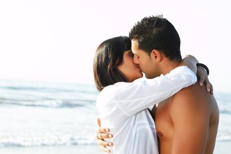 beso: cerca adorable retrato de una pareja de enamorados bes�ndose y abraz�ndose en el borde de la playa