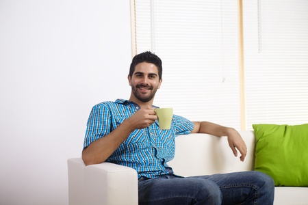 daily routine: Young man drinking coffee in a couch.