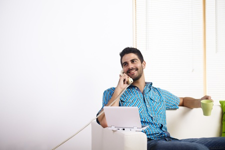 Young man drinking coffee and using laptop while talking on phone. photo