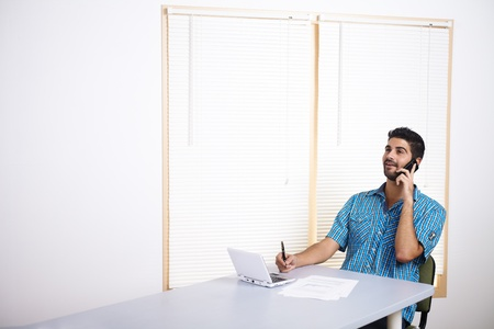 Young man talking on mobile phone while working. photo