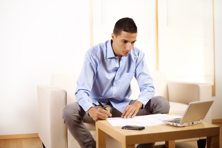 Portrait of a young businessman working with laptop and documents. photo