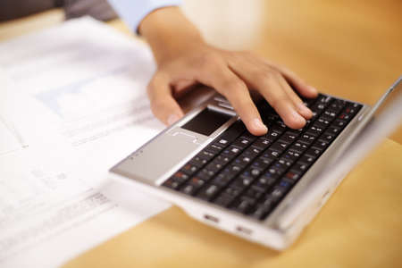 Hand of a young businessman working with laptop and documents. photo