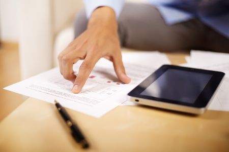 reviewing documents: Hand of a young businessman reviewing documents.