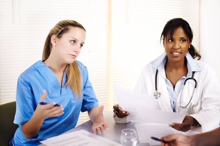 Portrait of a doctor talking on a meeting with two of his co-workers photo