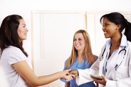 Portrait of a doctor with one of his co-workers and greeting a patient