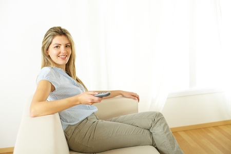 Portrait of a young woman using a control remote at home  photo