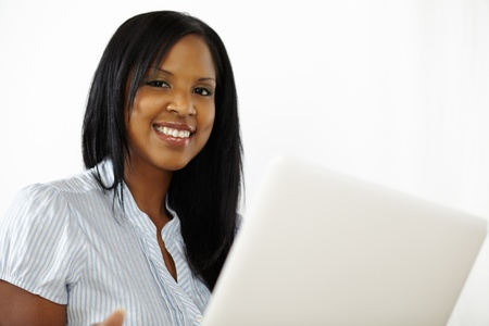 Portrait of a cute young woman using a laptop while smiling to you