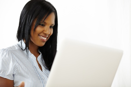 Close up portrait of a cute young woman working on laptop while smiling photo