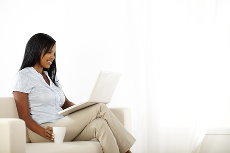 Portrait of a beautiful young woman working on laptop while resting on sofa photo
